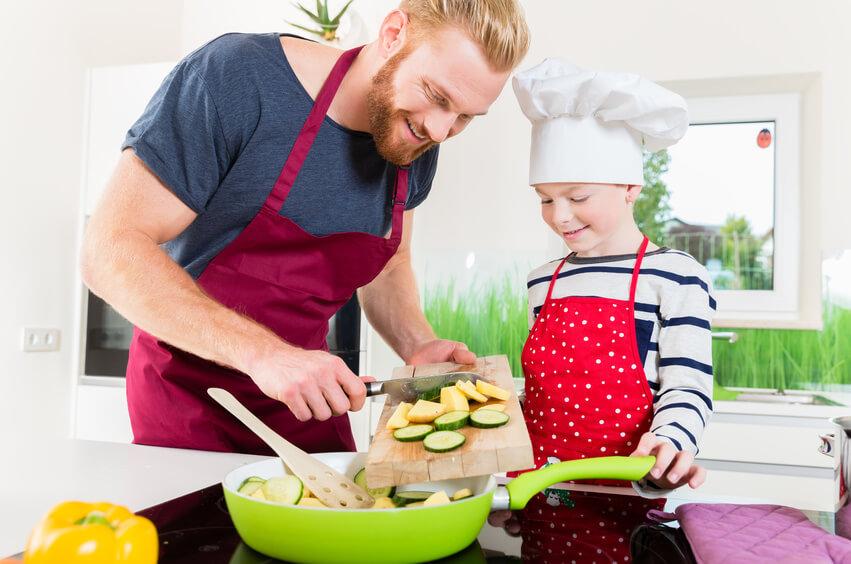 Mann mit Kind beim Kochen